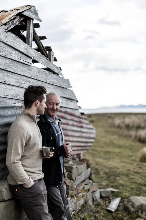Portrait photography of a father and son leaning against a shed