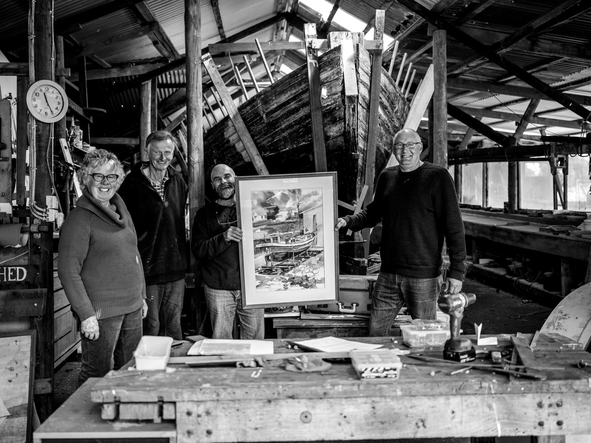 Helen and Peter Lindsay, Martin Wohlgemuth and Ian Hall of The Custodians of The Fancy, in the background you can see The Fancy's hull ready for restoration.
